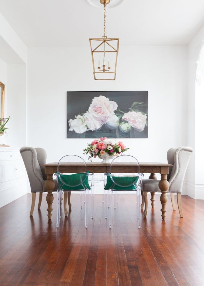 Ghost chairs with green cushions at wood dining table