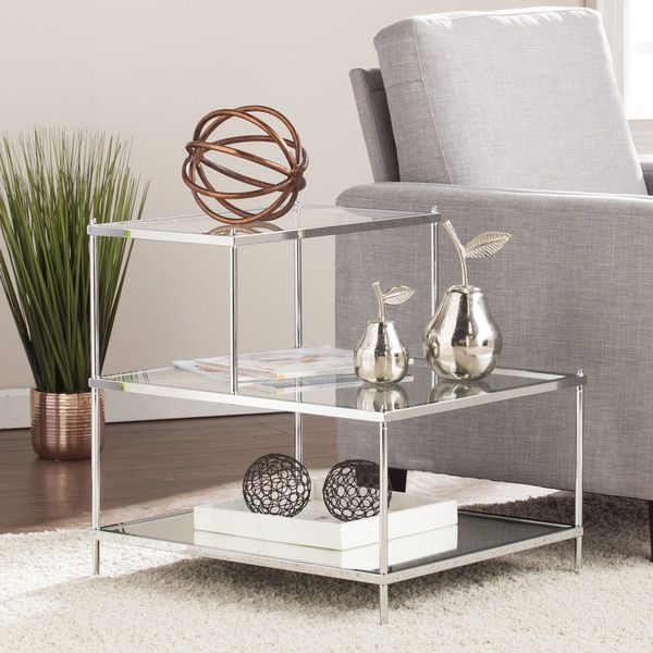 Glide into the glam life with this polished end table. Chrome-plated metal shines, mirror shimmers, and glass gleams in a stair step silhouette. Functional shelves hold everything from day time readin
