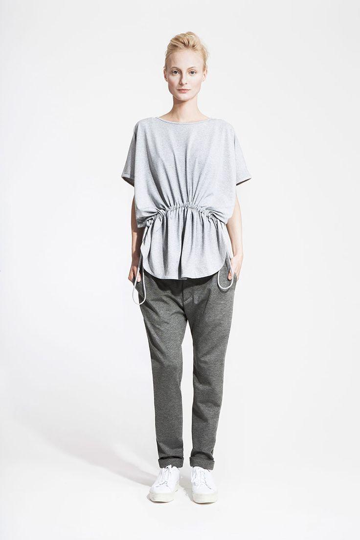 modelka oblecena do sedych teplakovych kalhot a svetlesedeho volneho kosiloveho tricka nadrhnuteho v pase