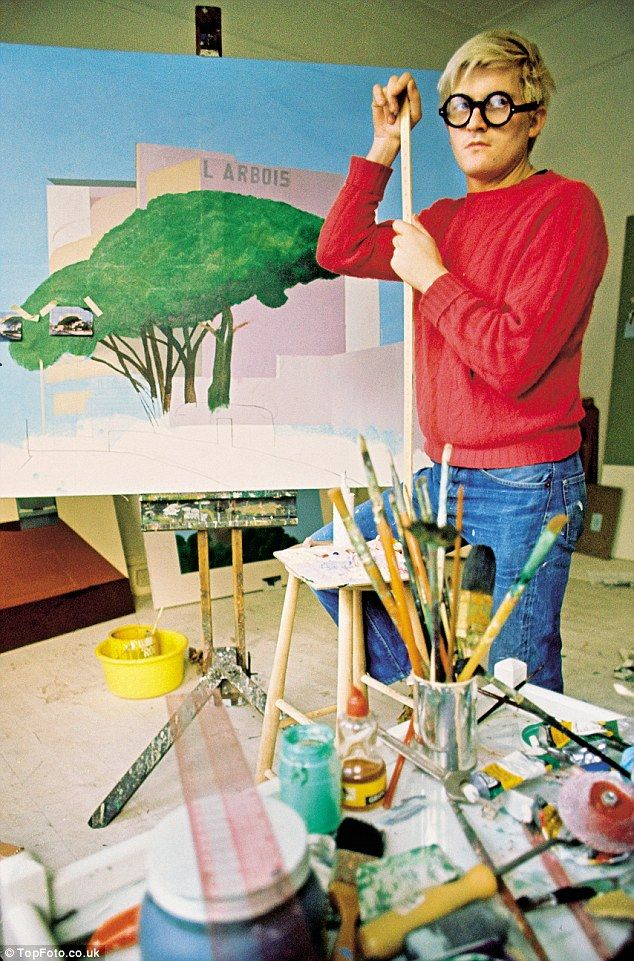 His sapphire-blue eyes sparkle mischievously behind the same type of round-framed glasses he wore as a student at the Royal College of Art in 1961. Above: Hockney at his studio in 1969