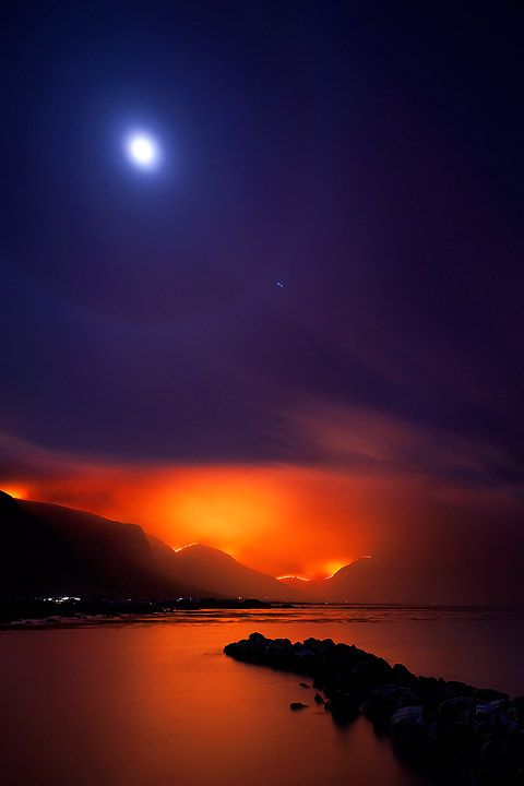 """Bettys Bay, South Africa Wildfires rage on the mountains of Bettys Bay as the moon calmly shines down on the placid waters. Moonlit Inferno by hougaard""""-"""".: Travel Planners, Southafrica, True Colors, Natural Beautiful, South Africa, Photo, Night Sky, Africa Travel, The Moon"""