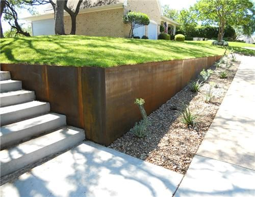 Modern metal retaining wall with planted stone bioswale.