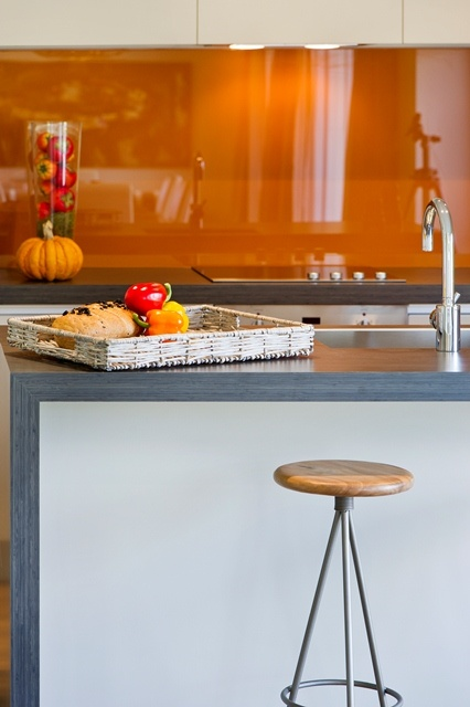 Autumn colours. Vibrant orange splashback gives this kitchen punch.