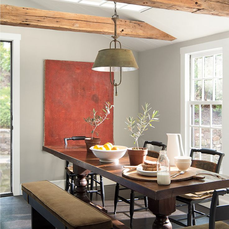 Dining room with neutral gray walls and exposed ceiling beams