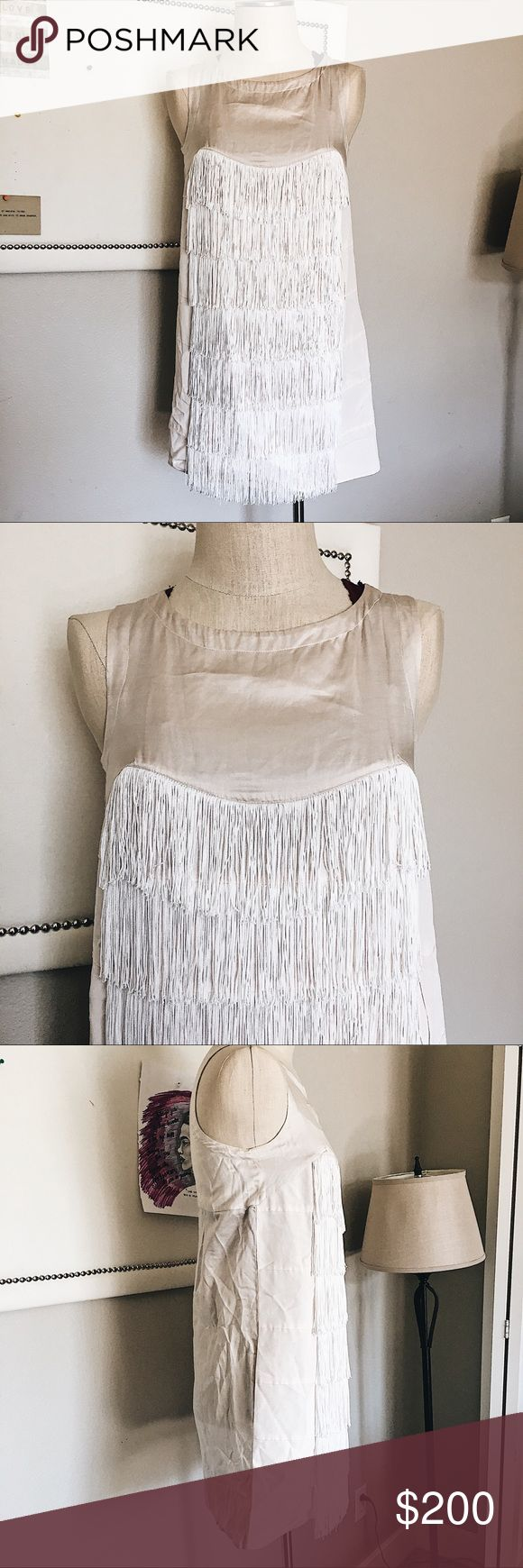 Nude Fringe Dress This dress is fun and flirty, the perfect night out piece. It is a nude beige color with white fringe going down the front. The neck is high giving the piece a sophisticated style. The fringe adds gorgeous movement and shape to the piece. Going down the front, the fabric is layered along with the fringe creating almost ruffles. There is a zip closure up the back of Dress. It is in great condition besides some slight yellowing under the arms. Luxury brand See by Chloe, Size…