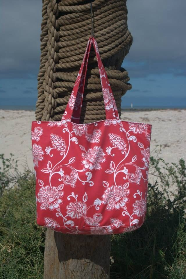 Red floral beach bag lined with white cotton fabric. Outer made from exterior upholstery fabric.  Measures approx 51x41x15cm. $30.00 each