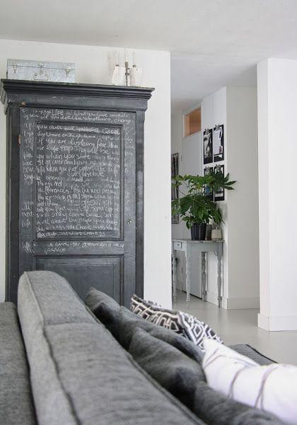 sofa gris... almacenaje de pared para salon y el detalle de la mesita detrás con los clipboards en la pared y las plantes
