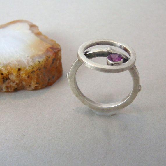 Deze moderne ring beschikt over een Rhodolite Garnet die een roze-paars rode kleur is. De geborstelde afwerking van de sterling silver ring maakt echt de sprankelende garnet pop! De ring bestaat uit een cirkel van sterling zilver, perfect rusten op de top van de schacht van de ring. De granaat rust binnenkant van de bovenste cirkel. De ring maatregelen een US maat 6-3/4 de schacht ring 4 toegevoegd heeft bultjes rond de buitenkant als een accent. Ik heb hand gemaakt dit hele ring en de i...