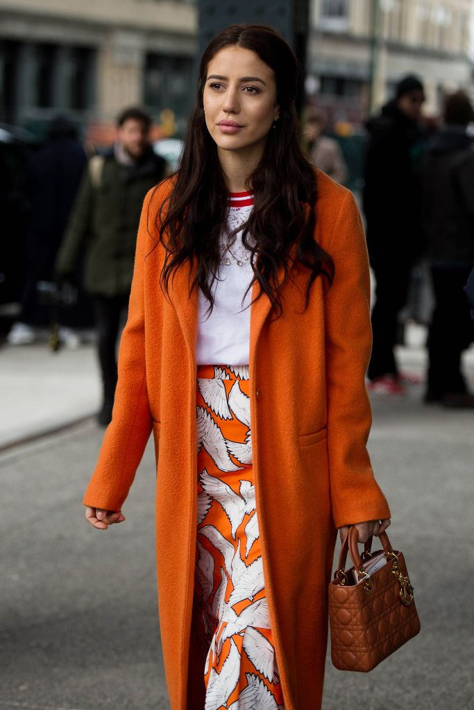Street style at New York Fashion Week Fall 2017: Bright orange coat with printed midi skirt and athleisure top