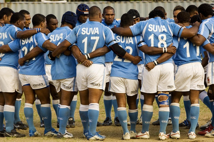 Suva rugby players linking bodies in circle at Albert park.  Fiji
