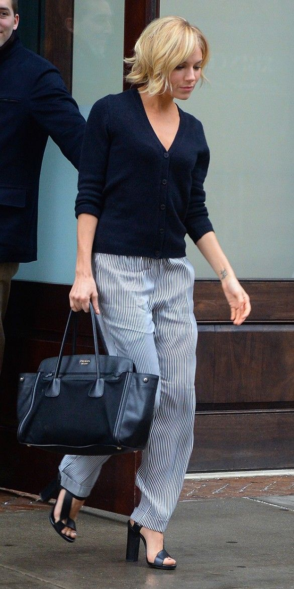 Sienna Miller in a cardigan, striped wide-leg trousers, and platforms