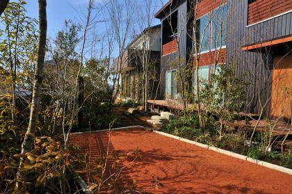 雑木の庭つくり日記@高田造園設計事務所  玄関ポーチから見た駐車場。木々の中に溶け込む駐車場は美しい庭の一部となります。   最近、駐車場の敷き込みに、古瓦を粉砕した再生チップをよく用います。 その第一の理由は、この素材の環境性能の高さにあります。陶器片ですので、透水性や保水性に非常に優れており、夏の日差しを受けても土中の湿気を吸放出して蓄熱することがありません。  また、吸水性がよいため、土地に応じて様々なものを吸着しながら、その土地らしい色合いに経年変化し、年月と共に味わいを増していきます。  また、チップの凹凸に枝葉の影がとても美しく映えることもこの素材の大きな魅力です。