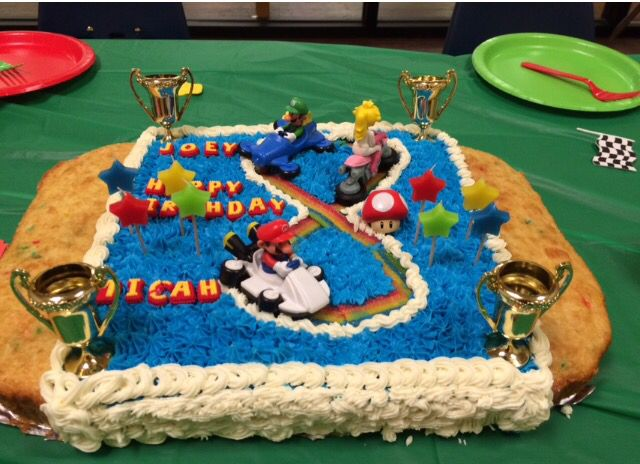 My twin boys turned 8. They wanted a Mario Kart 8 party and cake. I made rainbow road figure 8 out of sour strips. I left the two outer sides icing free for the birthday boy who doesn't like icing. Dollar tree party favor racing cups. Reused toys they already had (Mario, Luigi, Peach -all happy meal toys- and the mushroom). I've had the star candles from a clearance sale for a long time waiting for the perfect cake. They loved it.