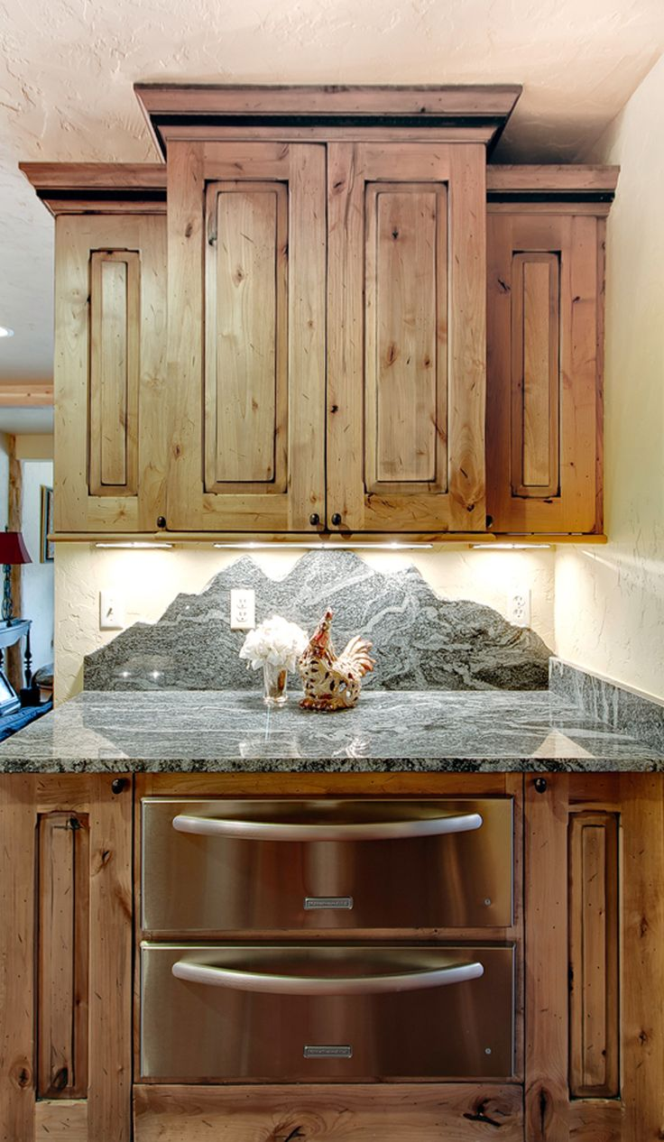The color of the cabinets and the mountainous back splash