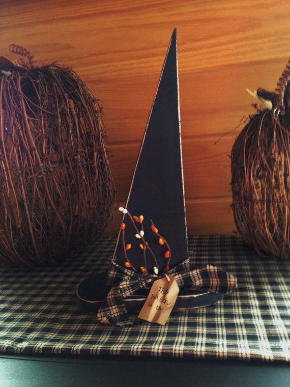 This primitive style wooden witch hat would look great in your home for Halloween! The hat measures approximately 6.5 l x 11.5 h x 3 w. Fall pip berries, black homespun fabric, and a hang tag saying The Witch Is In have been added for the primitive look.