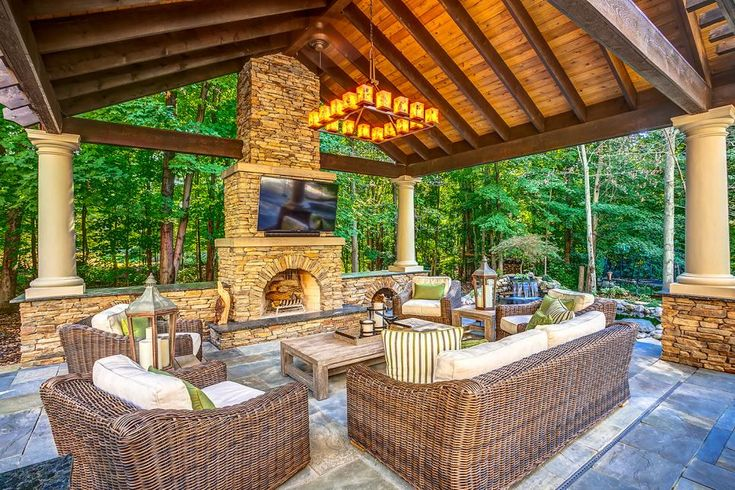 This covered contemporary outdoor living room was designed with rustic elegance. Natural stone surrounds a wood burning fireplace and extends up the chimney meeting the cedar roof. The brown wicker furniture is padded with light, neutral cushions and green accent pillows.