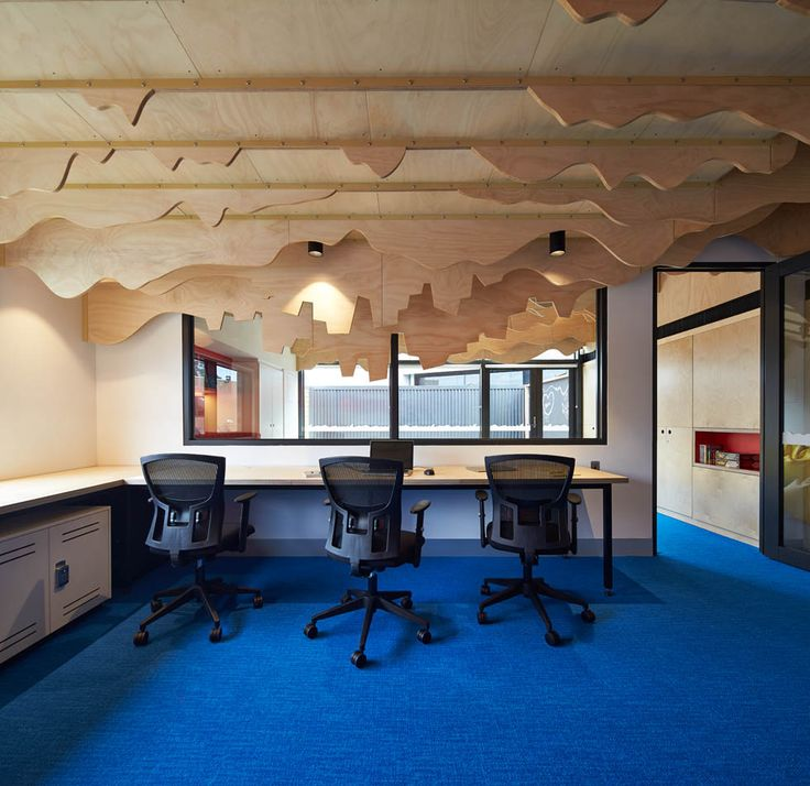 Blue-carpeted office space at the Cubbyhouse in Broadmeadows Children's Court with an up-side-down cityscape ceiling sculpted out of timber fins | Cubbyhouse by Mihaly Slocombe (2014-15) | Broadmeadows, Victoria, Australia  | Photo: Peter Bennetts