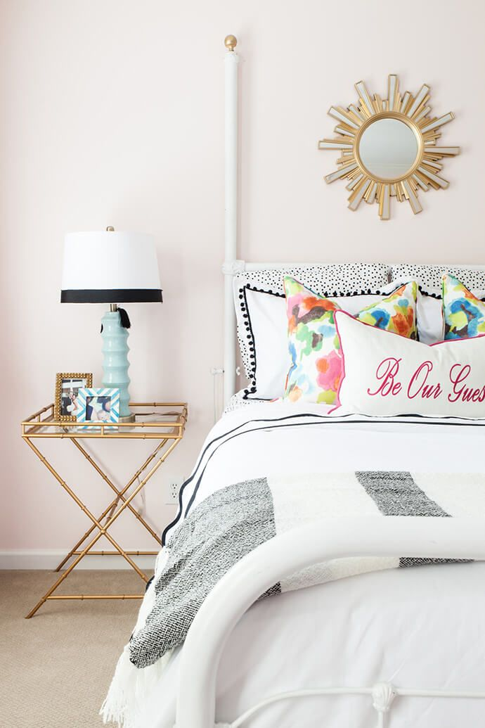 Feminine bedroom with pink walls, bright bedding and a gold touches