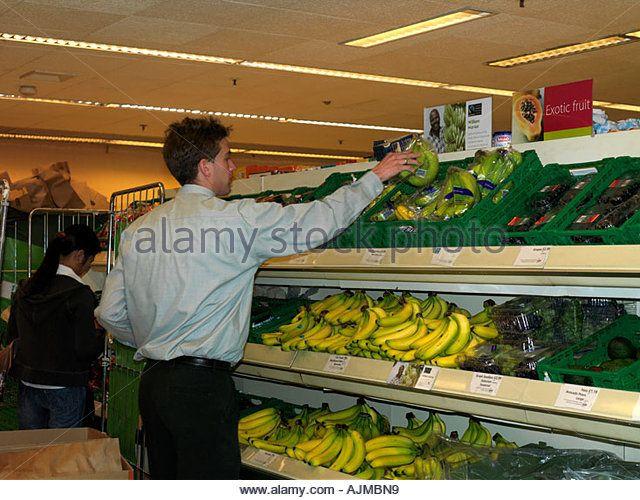 Stacking Fairtrade Bananas from Trolley in Waitrose Supermarket Epsom Surrey England - Stock Image