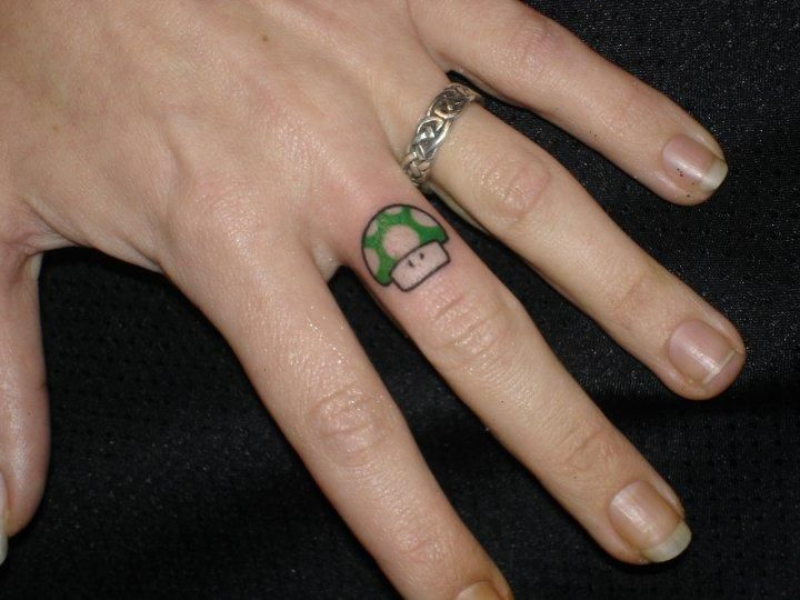 Small Mario Mushroom Green Ink Tattoo On Middle Finger