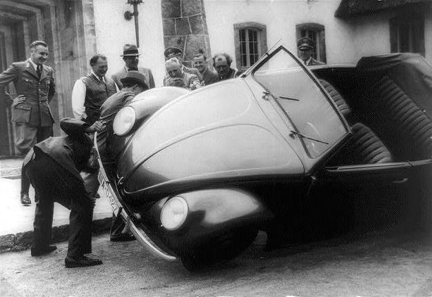 Ferdinand Porsche, second from the right, has helpers lift an early KdF-Wagen to show its front suspension to curious Germans.