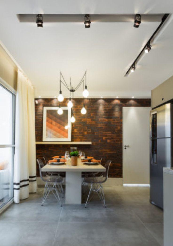 """Os arquitetos Débora Dalanezi e Marcello Sesso optaram por revestir o piso com um porcelanato que simula o cimento queimado. """"É um Studio de 37m² inspirado nos lofts nova iorquinos, por isso utilizamos o cimento, o tijolinho e trilhos de iluminação"""", explica Débora. """"O cimento é um material mais frio. Por isso, é fundamental prestar atenção aos detalhes do resto da decoração"""". Neste projeto, os detalhes incluem cortina branca, quadro em tons terra e luminária tipo pêndulo."""