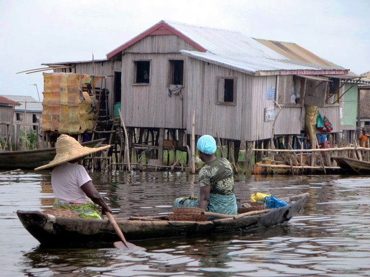 Tofinu women paddle through Ganvie on Lake Nokoue near Cotonou, Benin. The village formed in the 16th and 17th centuries as Tofinu people fled the mainland where they were hunted by Dahomey slavers.
