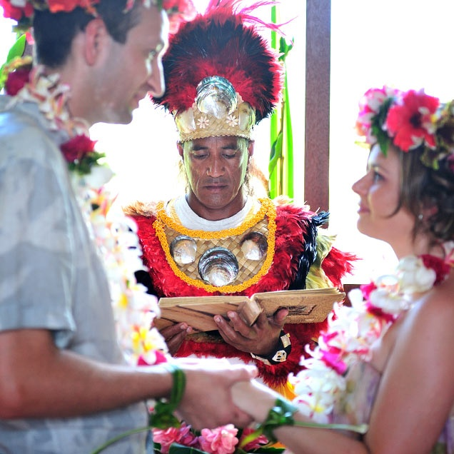 A traditionally dressed Polynesian priest leads the ...