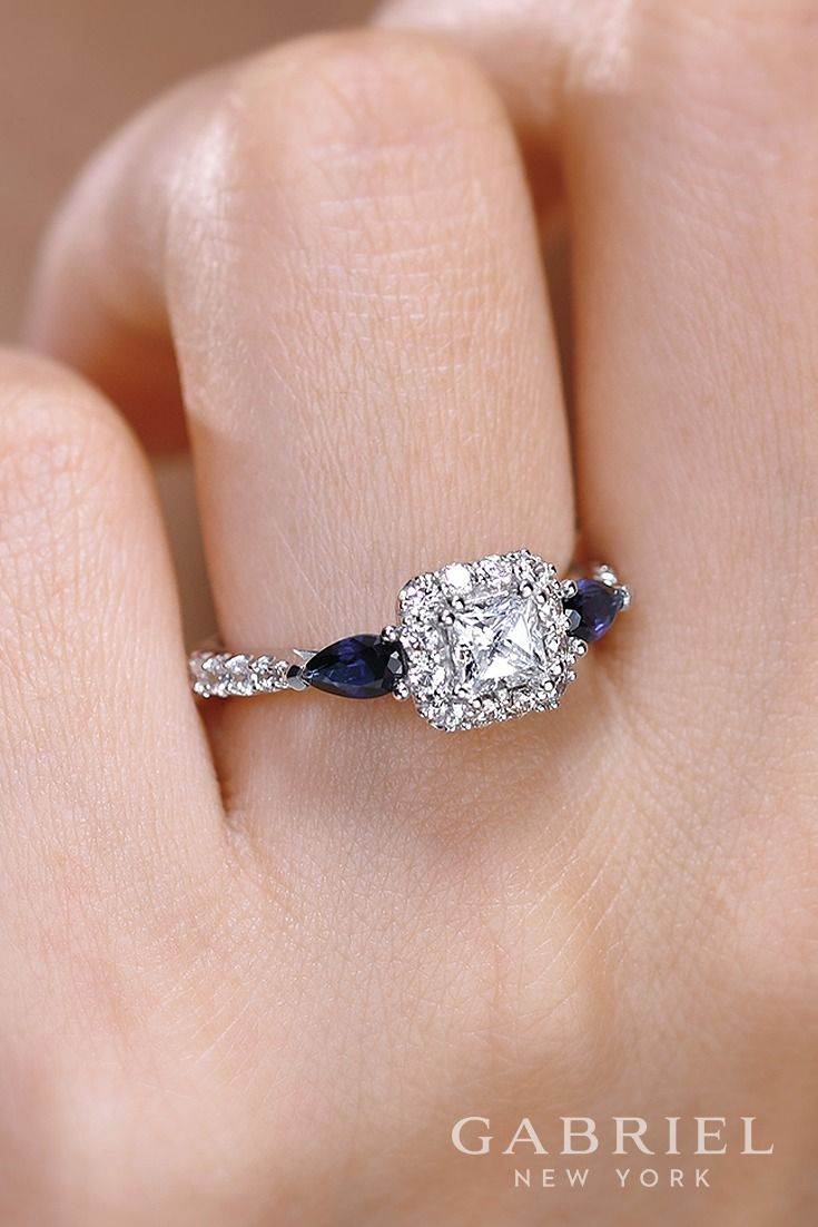 14k White Gold Princess Cut Halo engagement ring. In this captivating white gold engagement ring, a pair of deep blue pear cut sapphires frame a princess cut diamond in a diamond halo. Find more sapphire engagement rings here!
