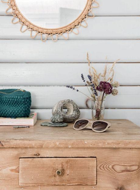 """""""Huset skal være enkelt og brugbart, men det skal også ose af hygge. Jeg har en svaghed for gamle møbler, og f.eks. den lille, blå mormor-sofa og et par andre arvesager giver huset lige det strejf af nostalgisk poesi, jeg synes, et sommerhus skal have, og med et par kontraster i form af en rå lampe, kernelæderstolen og et par nye ting bliver det romantiske ikke for meget."""" Det fine afsyrede bord med cluth, solbriller og nøgler er fra Camillas barndomshjem. Spejlet er et loppefund."""