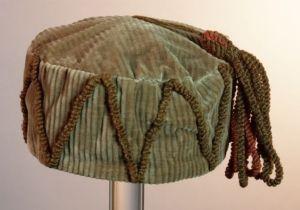1860-1900. Ronde bruin ribfluwelen fez, huismuts, smoking cap met kwast in rood en bruin