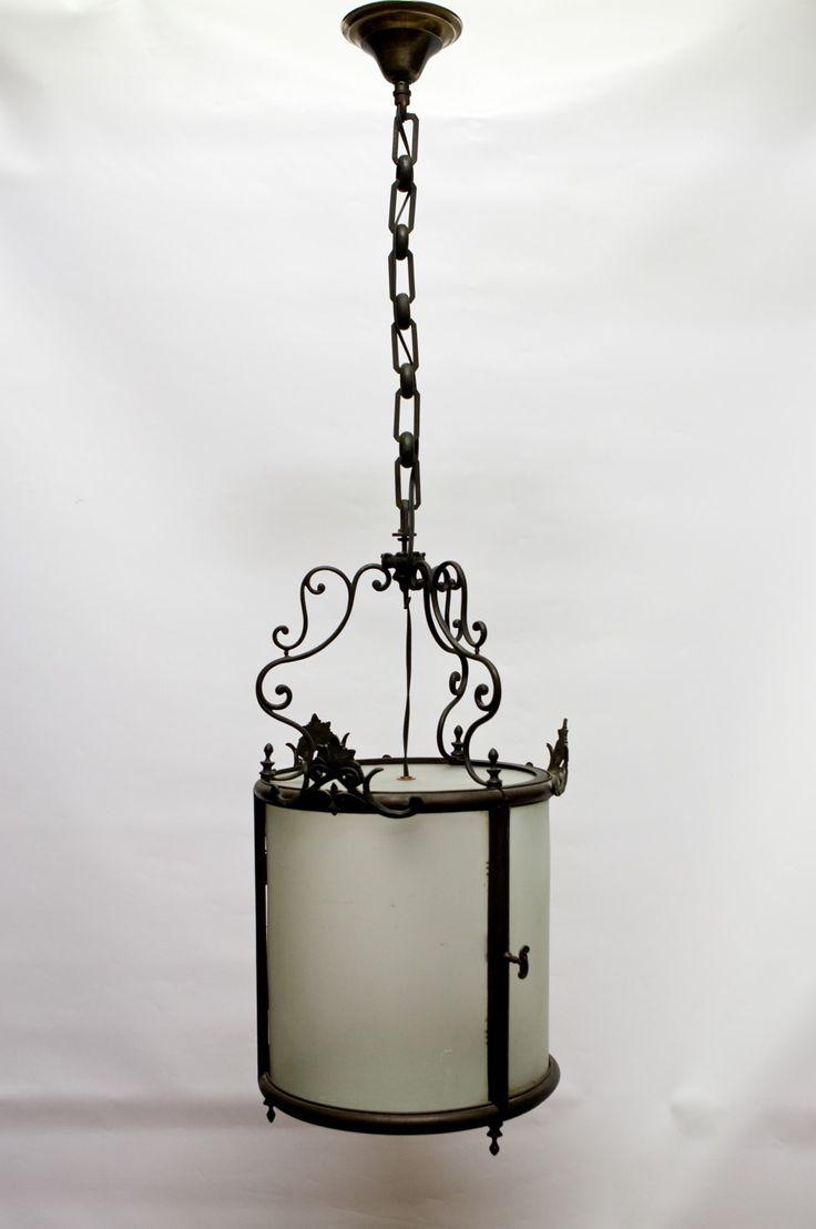 € 695,00 - Erg fraaie ganglamp / hallamp uit het begin van de vorige eeuw, zo rond 1910. Het is een vrij forse lamp, met aan alle kanten (mat)glas, dus ook onder en boven. De gloeilamp kun je vervangen door het deurtje open te doen (op een van de foto's is de greep van het deurtje vastgelegd). De hoogte kan worden aangepast door eventueel wat schakels uit de ketting te halen.