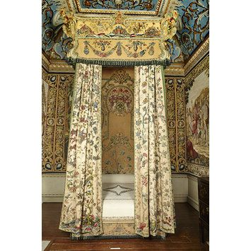 This impressive embroidered bed remains on loan to the house for which it was made, Houghton Hall in Norfolk. Visitors may see it there in the Embroidered Bedchamber. The headboard of the bed is decorated with the arms of Sir Robert Walpole, Britain's first prime minister (1721–1742), who built his palatial new house at Houghton between 1722 and 1731. In 1726 Walpole was the first commoner to be appointed as a knight of the Order of the Garter, the highest British civil and military honour