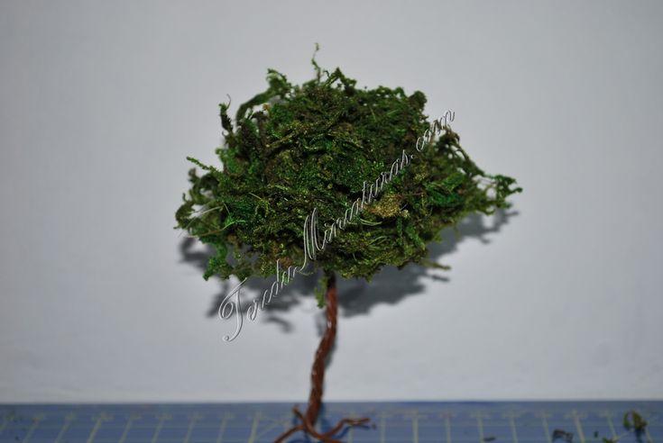 Materiales: Alambre con envoltura de plástico marrón, hilos de cuerda coloreados en verde, musgo artificial para belenes, cola. Empezamos cortando cuatro alambres de unos 15 cm. cada uno, los enrol…