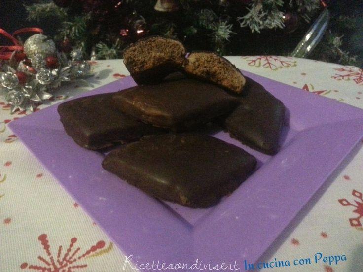 """I mustacciuoli sono dei dolci tipici campani a forma di rombo, ricoperti di glassa al cioccolato. I mustacciuoli si preparano nel periodo di Natale.  Ingredienti per circa 10-12 pezzi:  260 grammi farina """"00"""" 90 grammi zucchero 45 grammi miele 3 grammi bicarbonato di sodio 25 grammi cacao amaro 1 fiala aroma arancia 1 pizzico di sale fino 85 grammi acqua 10grammi pisto (6 grammi cannella + 2 grammi noce moscata + 2 grammi chiodi di garofano)  Per la glassa al cioccolato:  175 grammi…"""