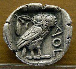"""Silver coin at the Museum of Fine Arts of Lyon depicting the owl of Athena (circa 480–420 BC). The inscription """"ΑΘΕ"""" is an abbreviation of ΑΘΗΝΑΙΩΝ, which may be translated as """"of the Athenians""""."""