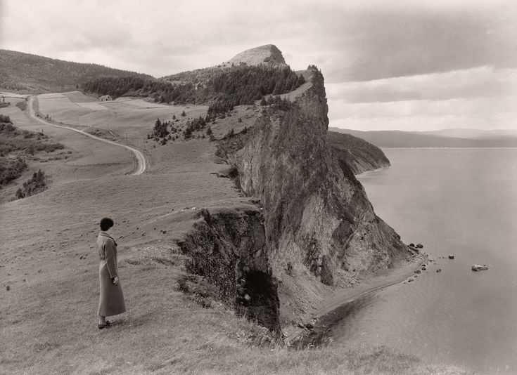 A woman stands before limestone cliffs in the Gaspe Peninsula, Quebec, September 1934. Photograph by B. Anthony Stewart