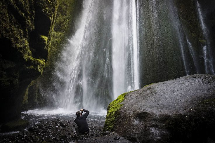 Photographer framing a shot at foot of powerful waterfall, Iceland