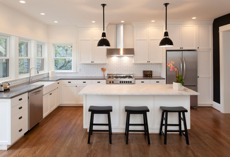 The pristine white of the kitchen island stands out in this space, with bold light marble countertop set against a trio of black wood bar stools. Rich hardwood flooring works with the light cabinetry and walls to brighten the room.