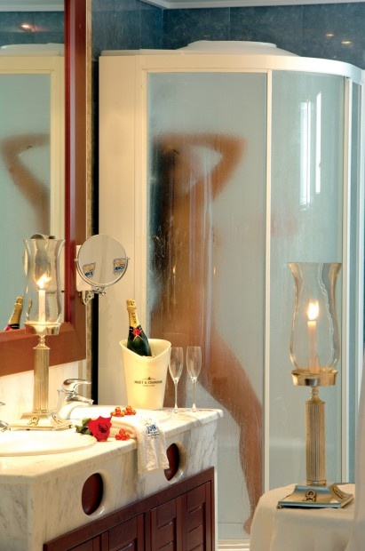 The modern bathroom hosts a Jacuzzi and steam shower, while the suite's spacious balcony overlooks a private beach and the vast Mediterranean Sea.