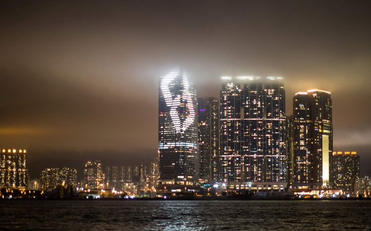 Japanese artist Tatsuo Miyajima's light installation for Art Basel Hong Kong entitled 'Time waterfall' is projected onto the facade of the International Commerce Centre (ICC) (centre) on the Kowloon waterfront
