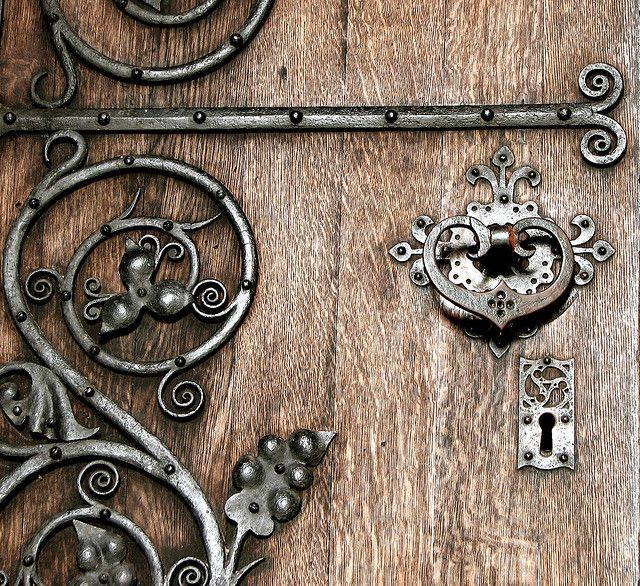 wrought iron scrollwork embellishing an old door ... hinge, knocker and keyhole