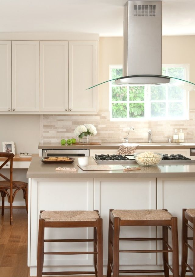 Island top gas stove and hood in white kitchen