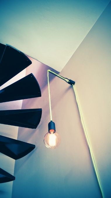 Our black colored wall lamp under a beautiful metallic stair. Imagine the light beams passing through the stairs at night.