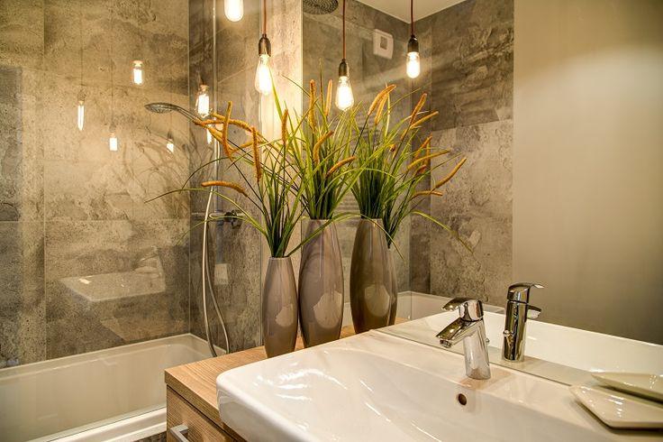 Minimalistyczne wnętrze łazienki z płytkami imitującymi beton. Oświetlenie  w postaci zwisających żarówek, które odbijają się w dużym lustrze powiększają przestrzeń i nadają jej klimatu, mimo tej surowości.