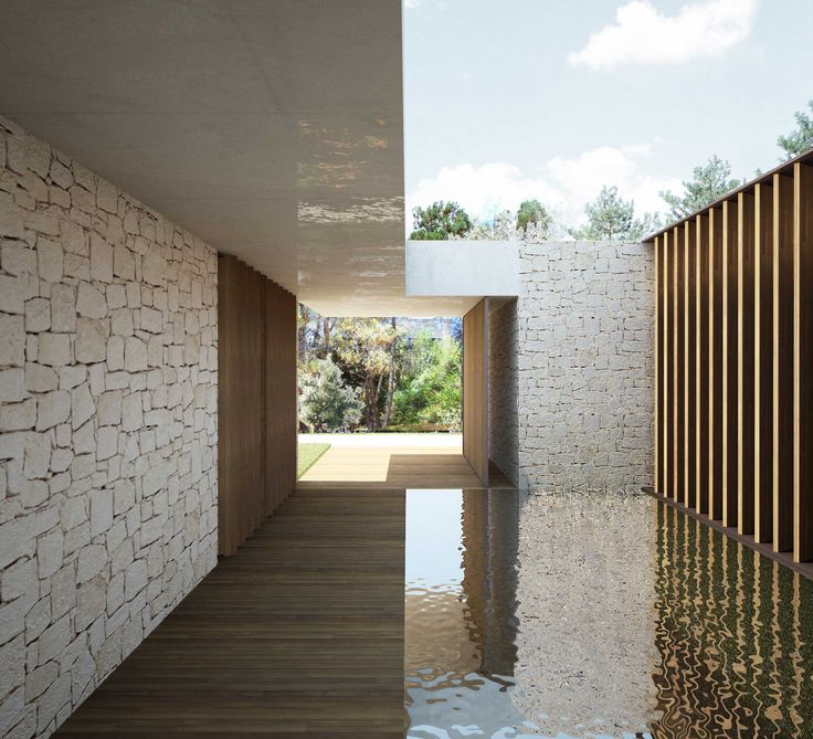 A large sheet of water stands out in this space and makes it look wider by reflecting the internal façade of the house and the sky.