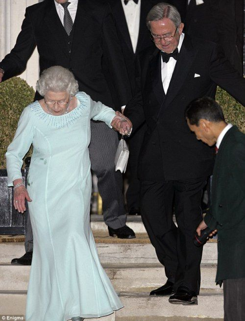 Queen Elizabeth II of England helped down steps by her cousin King Constantine II of Greece, at the end of his 70th birthday party