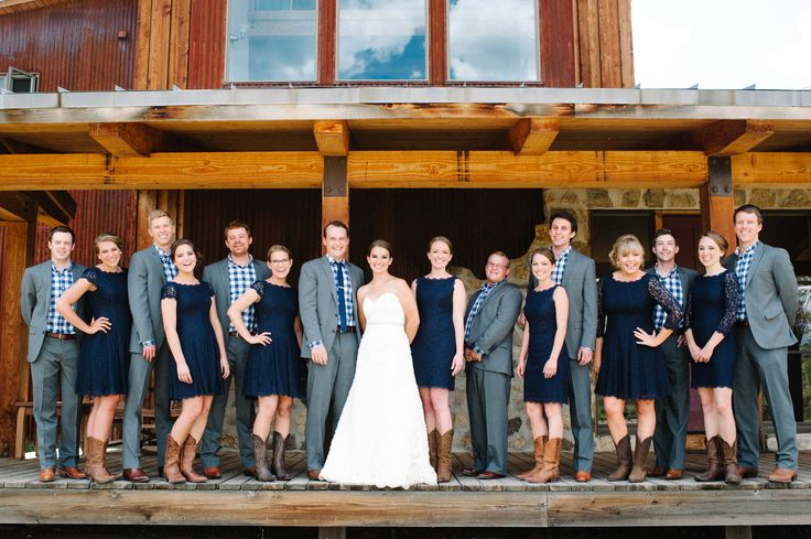 Rachel's bridesmaids wore navy lace bridesmaids dresses by Adrianna Papell for the shabby-chic wedding while the groomsmen wore gray suits with blue checkered shirts. Everyone completed their look with a pair of cowboy boots to fit the ranch location and rustic theme. // The Knot via Michelle Hart Photography