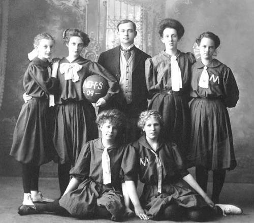 "Girls Basketball Team - 1909  Milton High School, North Dakota  Women's basketball goes back almost to the beginning of basketball, when students at Smith College first played the game, under the leadership of Senda Berenson.  Girl's basketball team, Milton High School, Milton, North Dakota, 1909.  One man, likely the coach, amidst six young women. One woman is holding a basketball under her arm, with letters ""M.H.S. '09."" No identification of people. Taken in studio with backdrop."