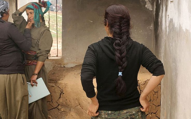 Female Kurdistan Workers Party (PKK) fighters talk in an area they use for baking bread at a base in Sinjar, March 13, 2015. Women fighters at a Kurdistan Workers Party (PKK) base on Mount Sinjar in northwest Iraq, just like their male counterparts, have to be ready for action at any time. Smoke from the front line, marking their battle against Islamic State, which launched an assault on northern Iraq last summer, is visible from the base. Many of the women have cut links with their families…